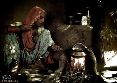 Rajasthani woman preparing a meal in her clay hut.