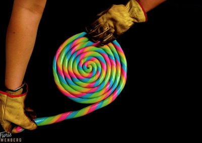 A rod of candy is rolled into a lollipop.